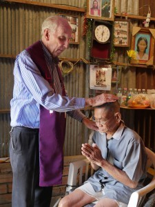 On his morning rounds in Anlong Kngan, Father Wynne gives a blessing to Oun Sophat, 76, a widower who is deaf and wheelchair bound and grateful for the visit. Maryknoll photo